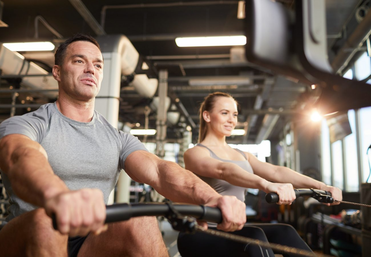 Fitness Couple Using Exercise Machine in Gym